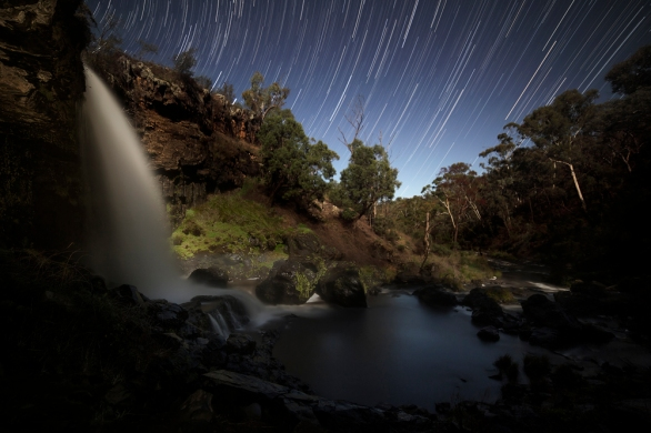 A waterfall over rocks and a river in the foreground and star trails in the night sky at the top of the image.