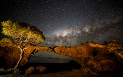 A rock formation that looks like a bridge, and a tree, in the foreground, and the starry night sky at the top of the image