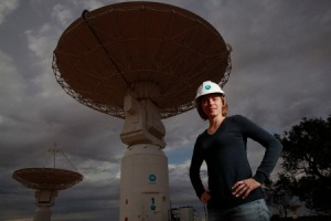 In the foreground a woman stands with her hands on her hips, there are large, while telescope antennas in the background.
