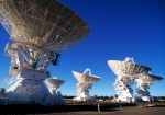 Five white telescope dishes on a bright, sunny day